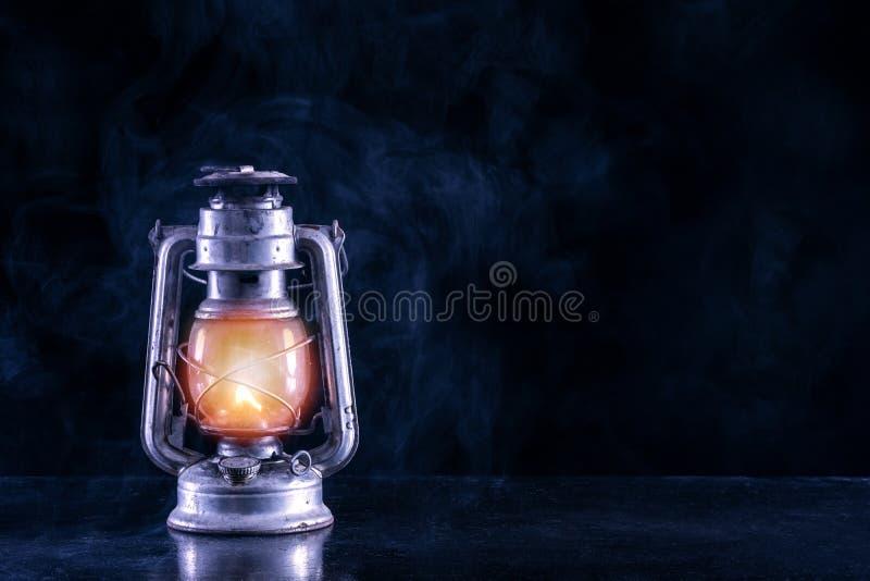 Linterna vieja del gas en la tabla negra y el paisaje de niebla y del humo de la oscuridad y de la noche fotos de archivo
