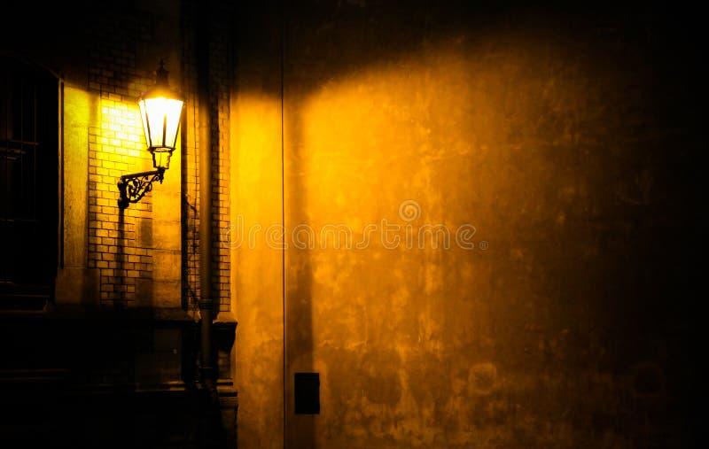 Linterna vieja que ilumina una pared oscura de la esquina del pasillo en la noche en Praga, República Checa fotos de archivo
