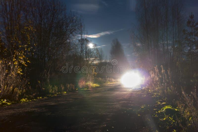 Linternas brillantes del coche inminente en el camino de la noche foto de archivo