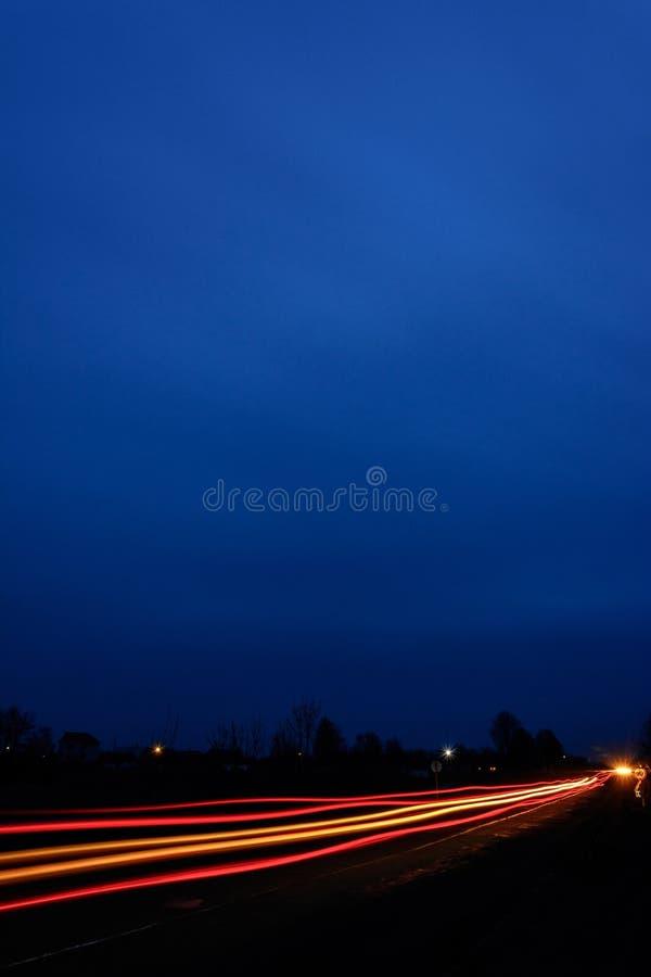Linternas de coches, tomadas con la exposición a largo plazo al fondo del cielo imagenes de archivo