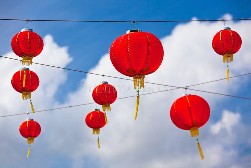 Linternas de papel chinas rojas contra un cielo azul fotos de archivo