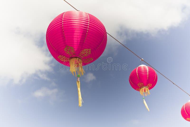 Linternas de papel chinas rosadas contra un cielo azul imágenes de archivo libres de regalías