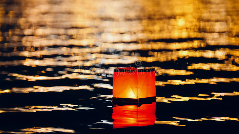 Linternas flotantes de la agua ligera en el río en la noche imagenes de archivo