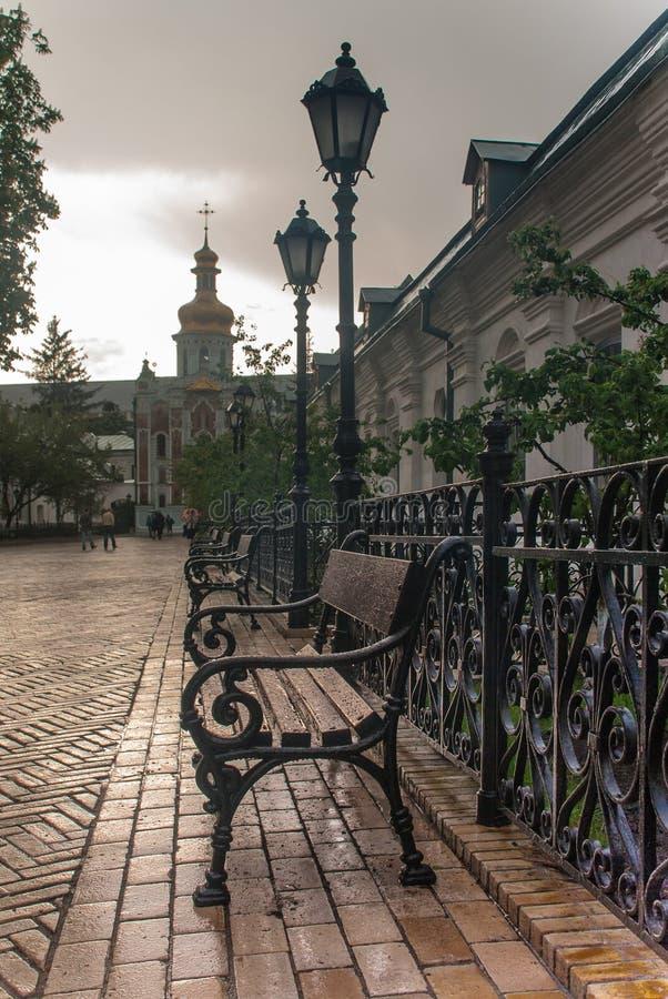 Linternas forjadas, bancos antiguos, decoración de Kiev Pechersk Lavra foto de archivo libre de regalías