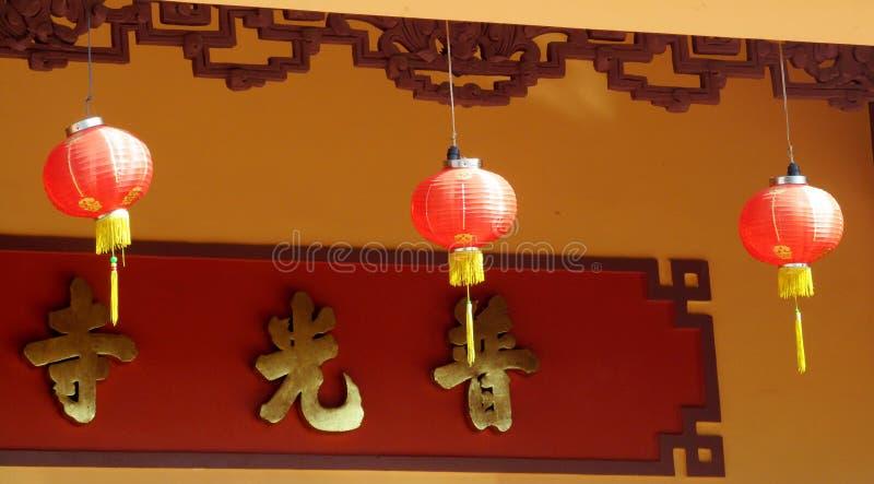 Linternas rojas asiáticas tradicionales en el patio de un templo budista imagen de archivo