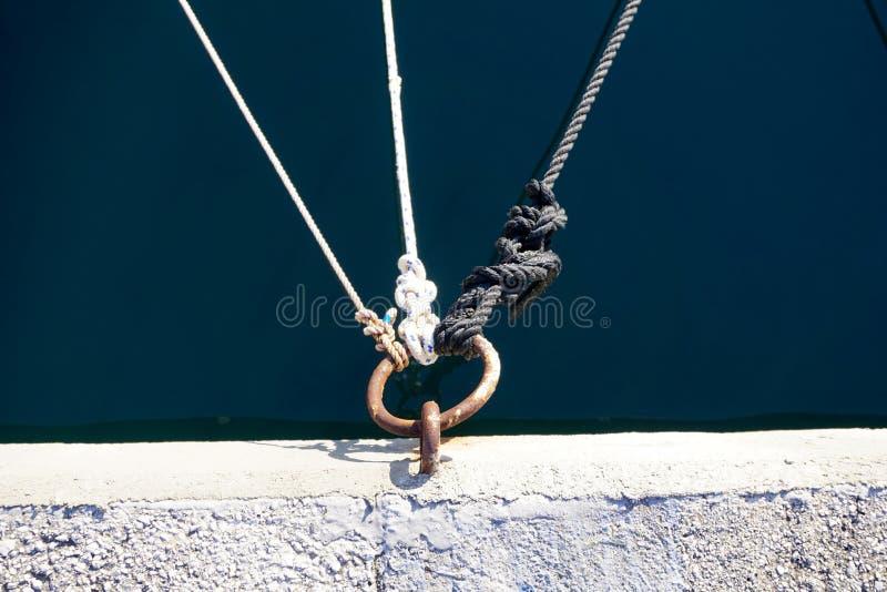Liny przywiązane do węzłów i przywiązane do metalowej obręczy na kamiennym nabrzeżu przy morzu obraz royalty free