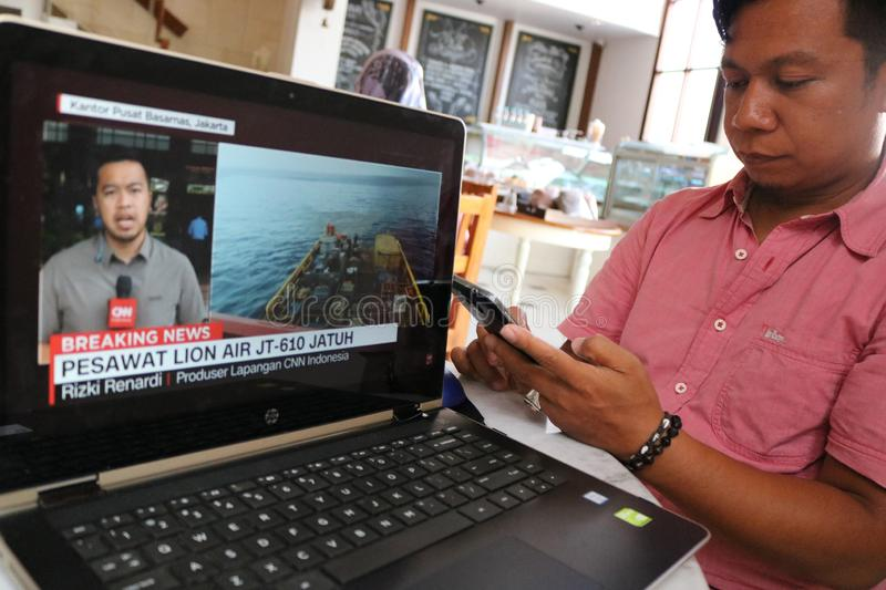 Lion Air JT 610 Falls in Indonesia. A resident watched the live broadcast of the fall of Lion Air JT 610 on a laptop in Makassar, Indonesia, Monday, October 29 royalty free stock photo