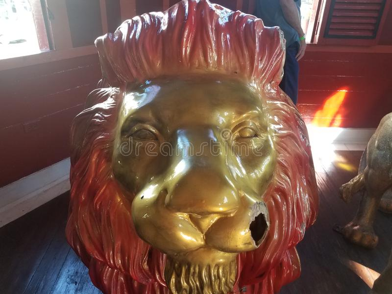 Lion animal statue with face painted gold and hole in face. Lion animal statue with face and painted gold and hole in face royalty free stock photo