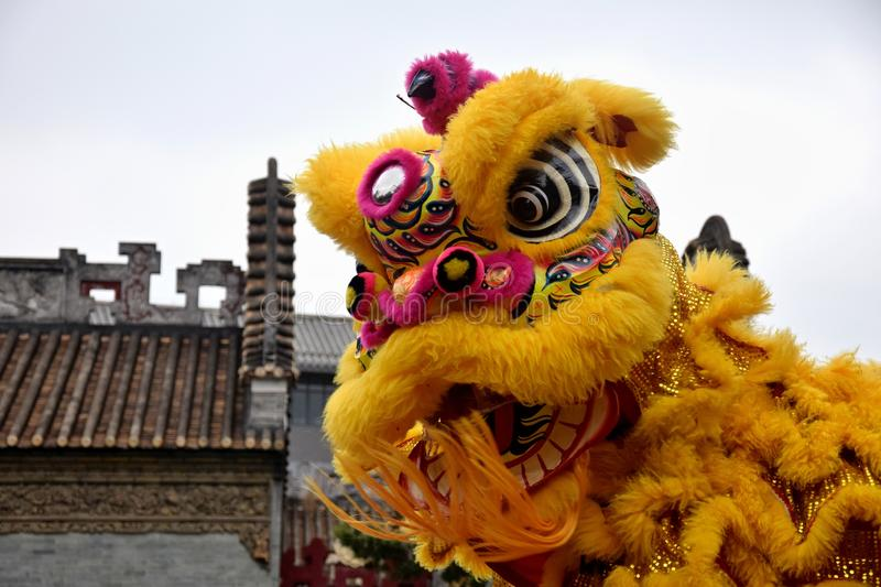 Lion dance costume with traditional chinese house in the background. royalty free stock photography