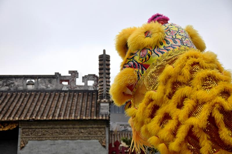 Lion dance costume with traditional chinese house in the background. Lion Dance is a form of traditional dance in Chinese culture in which performers mimic a stock image