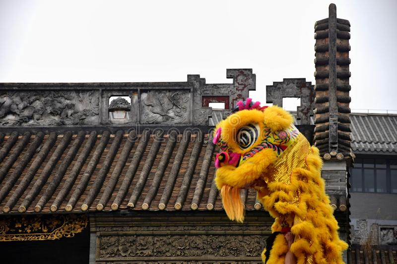 Lion dance costume with traditional chinese house in the background. Lion Dance is a form of traditional dance in Chinese culture in which performers mimic a stock photos