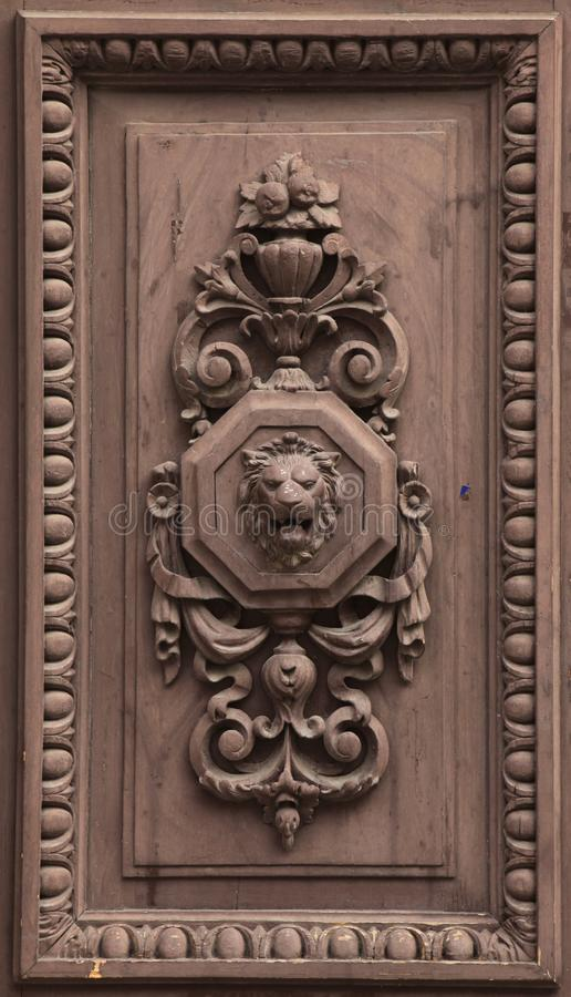 Lion depicted in the wooden relief. On the door of the dwelling house in Prague, Czech Republic stock images