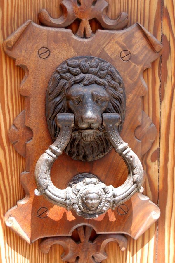 Lion door knocker. Lion head door knocker on an ornate wooden door royalty free stock image