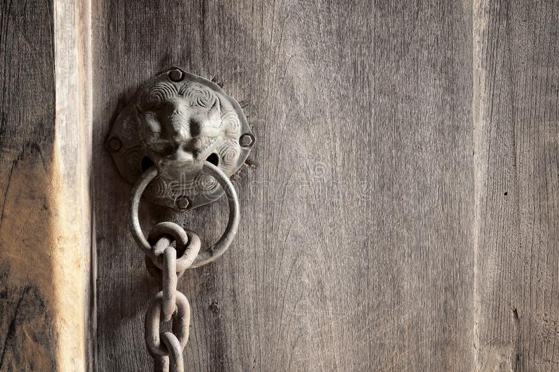 Lion head as a knocker metal handle on a old wooden door stock photos