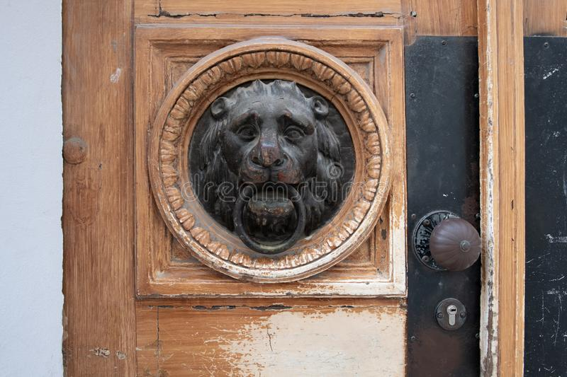 Lion head door knocker on wooden door stock image