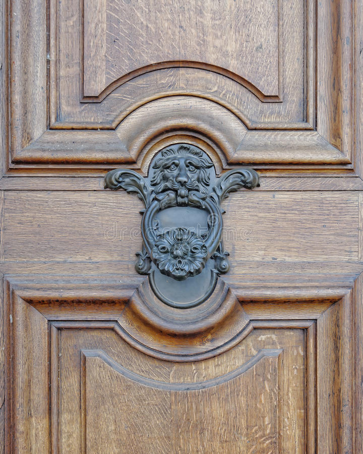 Lion head knocker on wooden door royalty free stock photography