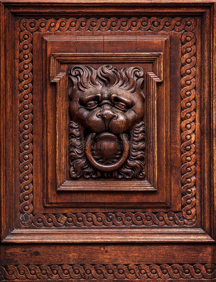 Lion Head som träskulptur i gammal dörr royaltyfria bilder