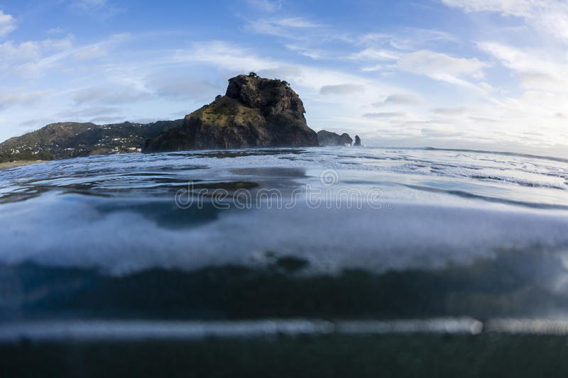 Lion Rock, North Piha, Auckland, New Zealand. Piha Beach's iconic Lion Rock, taken from a swimmer's perspective in the water, at North Piha stock image
