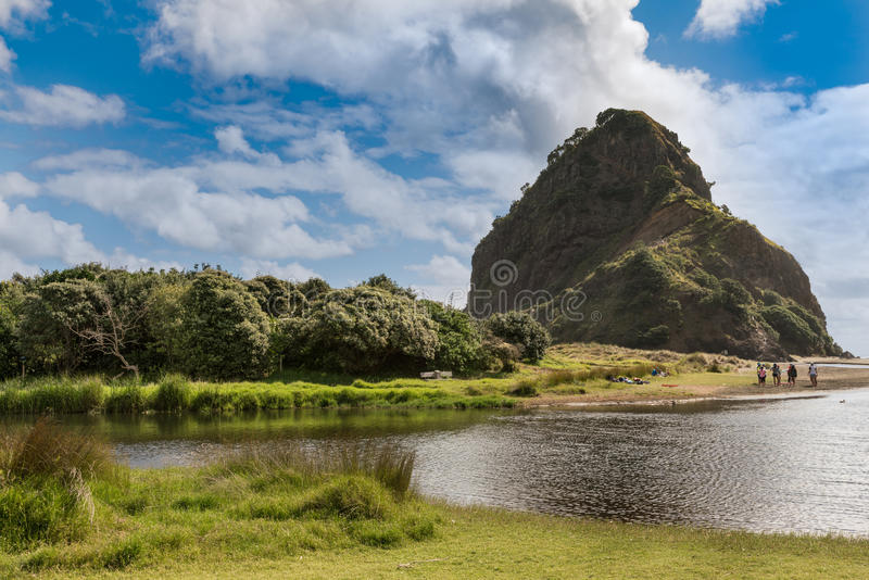 Lion rock on Piha Beach seen from creek. Auckland, New Zealand - March 2, 2017: Lion rock at sandy Piha Beach under blue sky with white clouds. Seen from his royalty free stock images