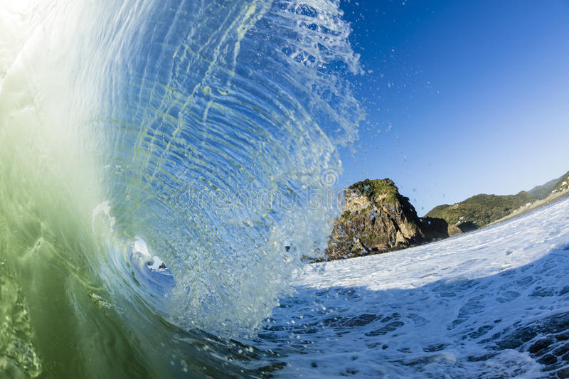 Lion Rock, Piha. Iconic Lion Rock shot from the surf, with a big wave breaking at Piha Beach, Auckland, New Zealand royalty free stock image