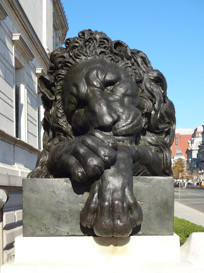 Lion Statue. Sculpture of a lion resting on its paws staring at the viewer intently stock photography