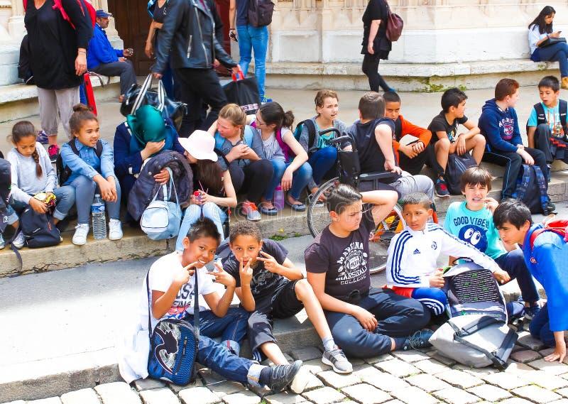 Lione, Francia - 16 giugno 2016: gruppo di bambini che si siedono sui punti la cattedrale nella vecchia città fotografia stock libera da diritti