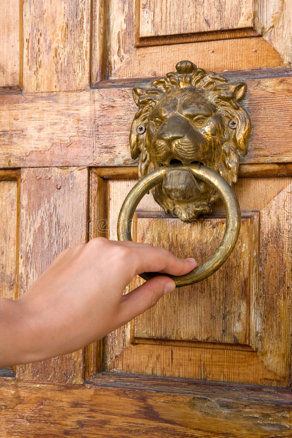 Lionhead knocker. Lionhead door knocker with ladies hand. Wooden door royalty free stock image