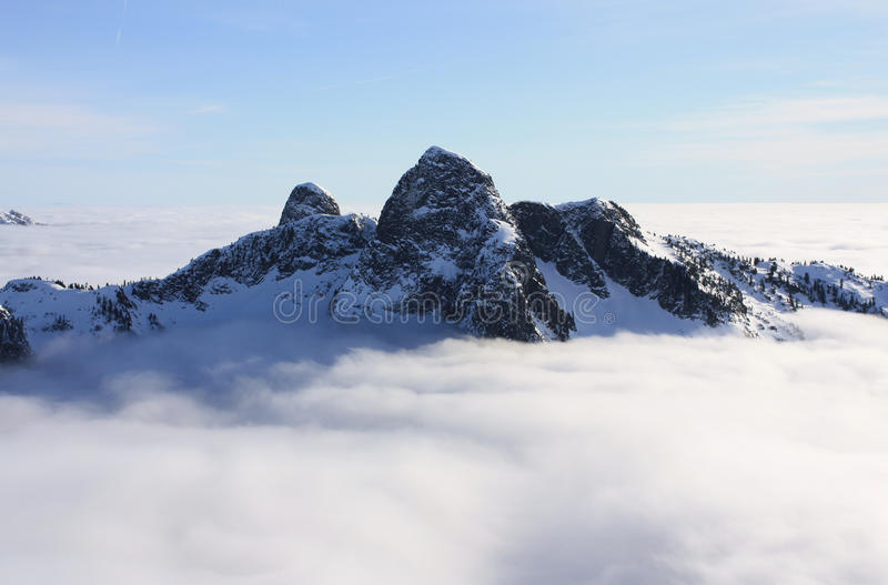 The Lions above the clouds in North Shore Mountains, BC, Canada. These two mountains can be seen from many locations around Vancouver and they stand as royalty free stock photography