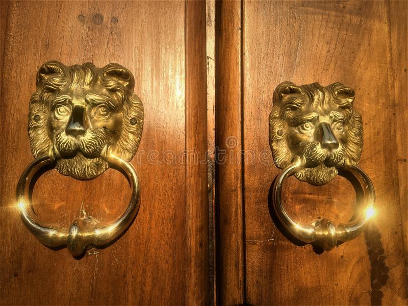 Lions d'or, doubles visages, détails de porte photo stock
