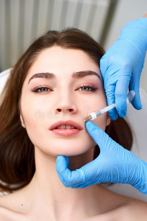 Lip Augmentation. Closeup Of Beautician Doctor Hands Doing Beauty Procedure To Female Lips with Syringe. Young Woman`s royalty free stock photography