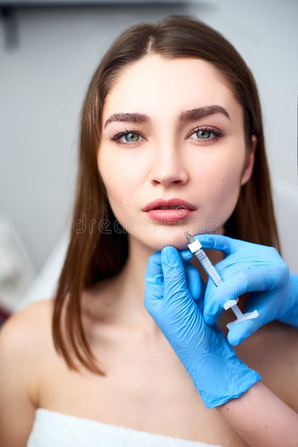 Lip Augmentation. Closeup Of Beautician Doctor Hands Doing Beauty Procedure To Female Lips with Syringe. Young Woman`s royalty free stock images