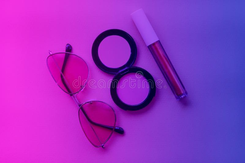 Lip gloss, rouge and sunglasses are toned on trendy neon colors – pink, violet and blue. Makeup and fashion concept. Flat lay stock photos