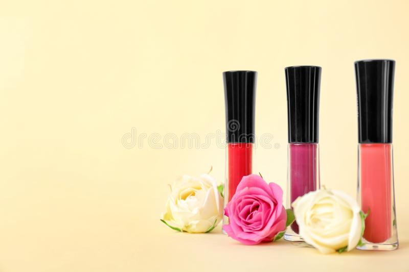 Lip glosses and flowers. On color background royalty free stock photos