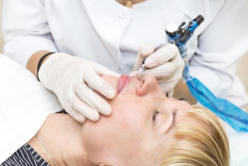 Lip tattoo process. Lip tattoo woman in a beauty salon process stock photography