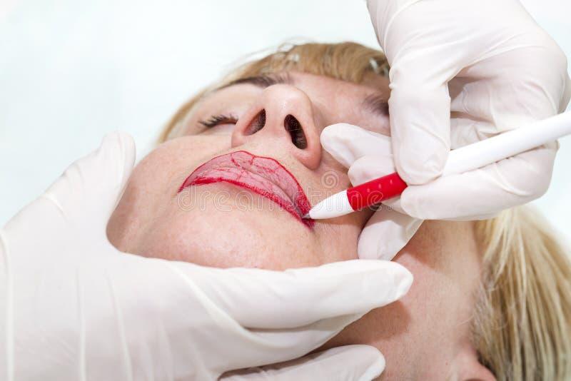 Lip tattoo process. Lip tattoo women in a beauty salon process royalty free stock photography