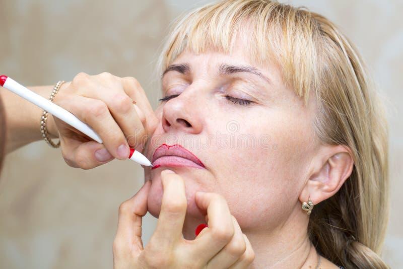 Lip tattoo process. Lip tattoo women in a beauty salon process royalty free stock photos