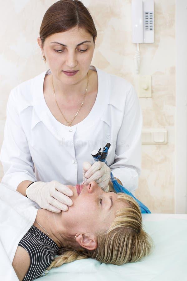 Lip tattoo process. Lip tattoo women in a beauty salon process stock photography