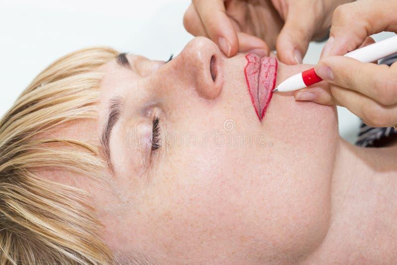 Lip tattoo process. Lip tattoo women in a beauty salon process royalty free stock images