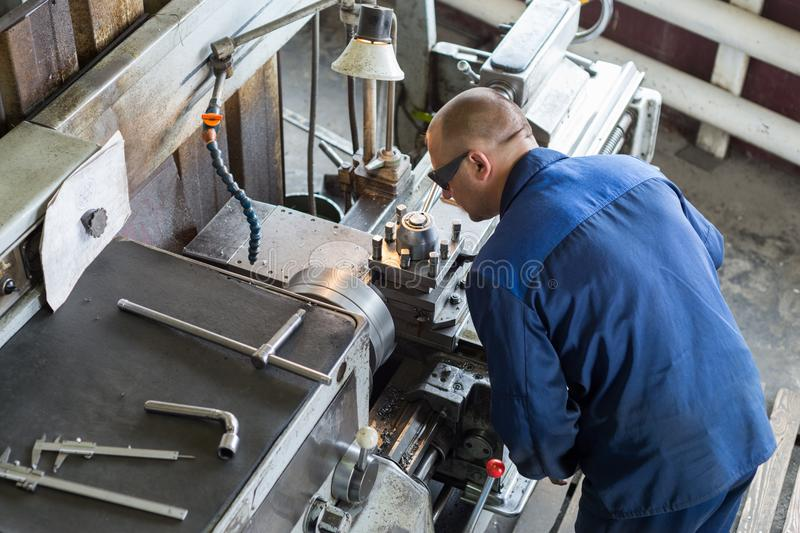 Turning works. The turner makes a metal part on a mechanical lathe. royalty free stock image