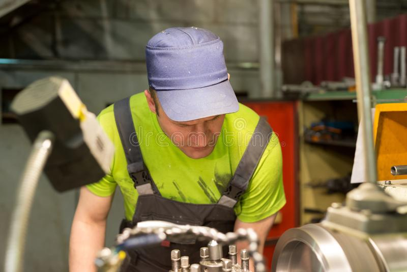 A young turner processes a metal workpiece on a mechanical lathe. stock image