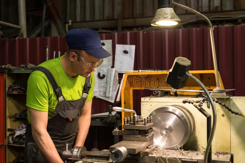 A young turner processes a metal workpiece on a mechanical lathe. stock images