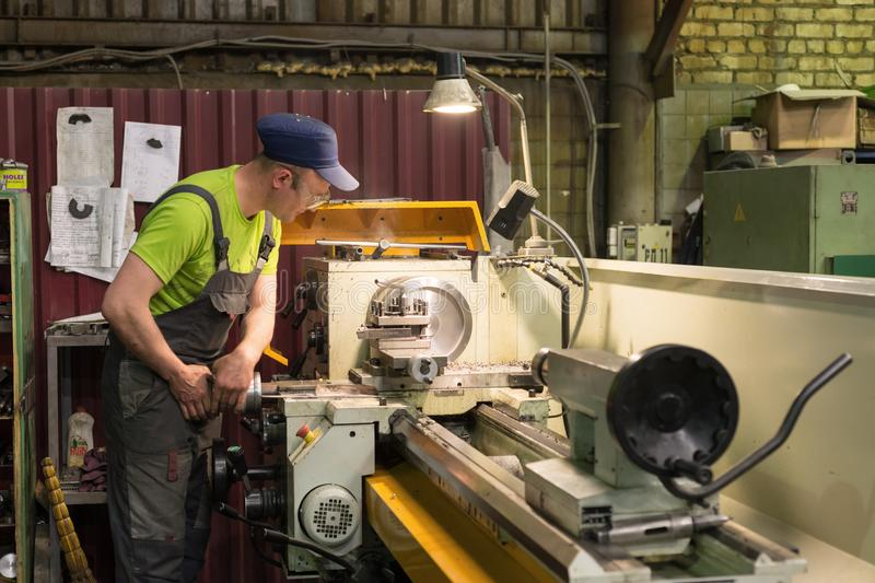 A young turner processes a metal workpiece on a mechanical lathe. royalty free stock images