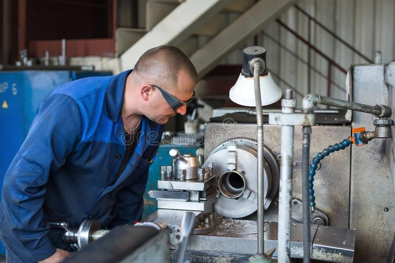 A young turner processes a metal workpiece on a mechanical lathe. stock photo