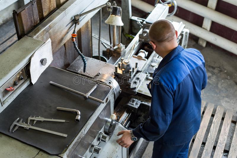 A young turner processes a metal workpiece on a mechanical lathe. stock photography
