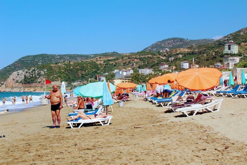 Lipiec, 2017 - ludzie odpoczywają na deckchairs w cieniu plażowi parasole na Cleopatra plaży Alanya, Turcja fotografia royalty free