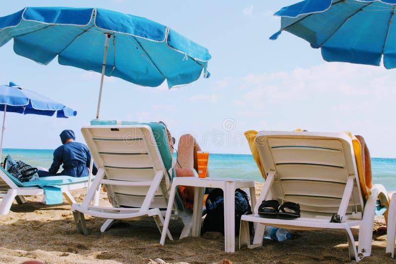Lipiec, 2017 - ludzie odpoczywają na deckchairs w cieniu plażowi parasole na Cleopatra plaży Alanya, Turcja zdjęcie stock