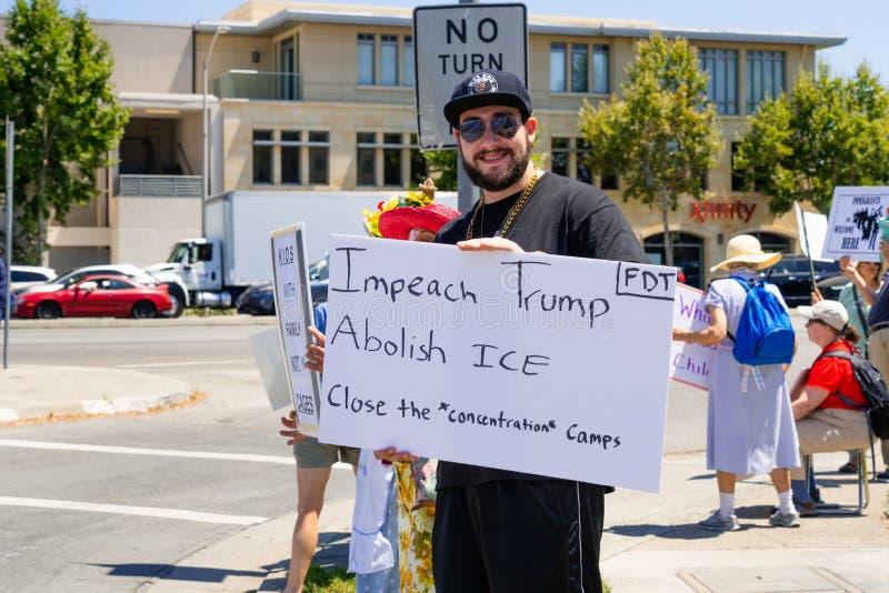 Lipiec 26, 2019 Palo Alto, CA, usa/- protestujący trzyma znaka z wiadomościami Obala prezydenta atut «, «Znosi lód «i «Zamyka con fotografia royalty free