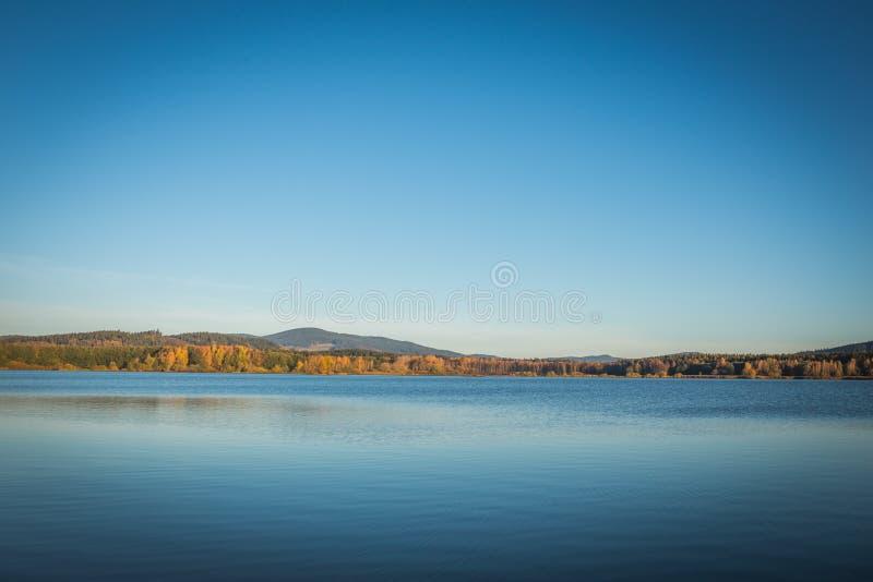 The Lipno Dam - Cerna v Posumavi, Czech Republic in a bright summer day. The lake is calm, has clean blue water. There. The Lipno Dam in a bright summer day. The stock photography