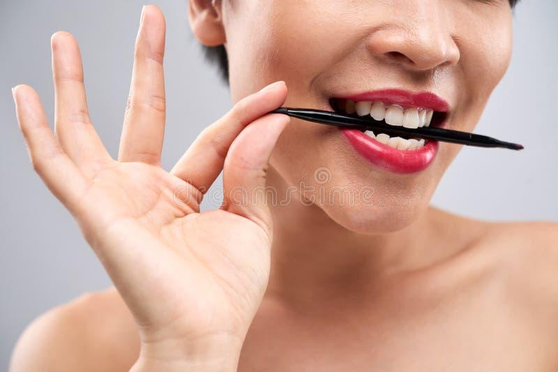 Lippenborstel in mond van jonge vrouw royalty-vrije stock afbeelding