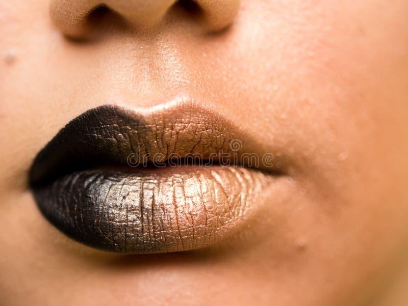 Lippenmake-up Modisches Schwarzes der Schönheitshaute couture mit Goldfarbsteigungslippenmake-upprobe, sexy Mundnahaufnahme stockfotos